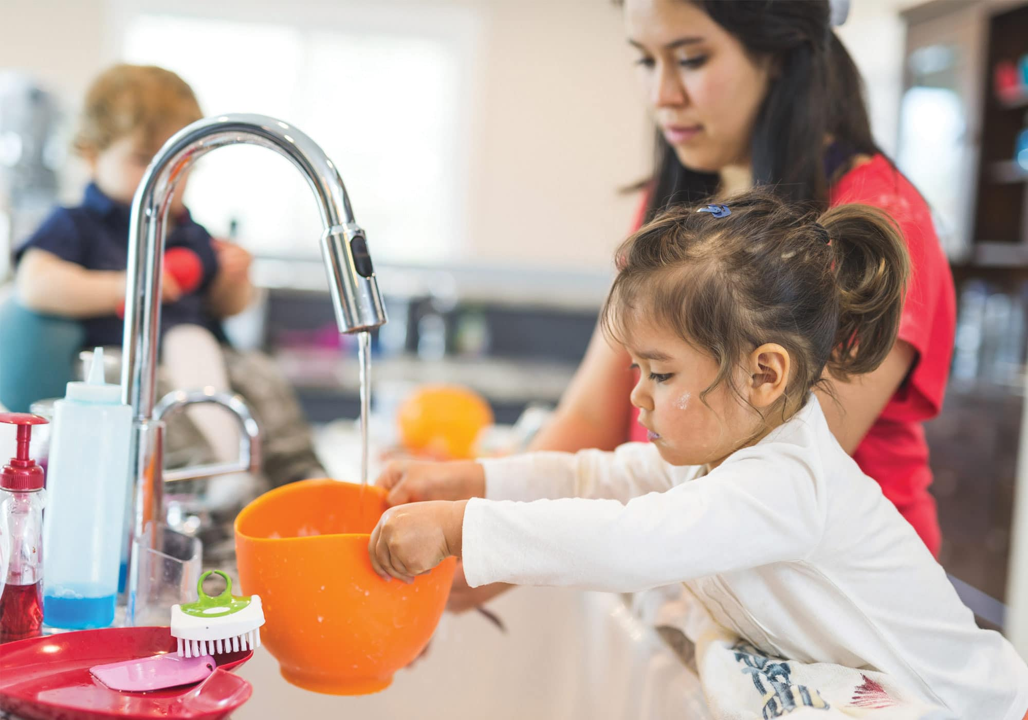 little girl helping mom in kitchen