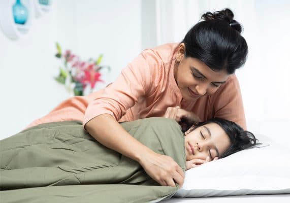 Mom putting daughter to bed
