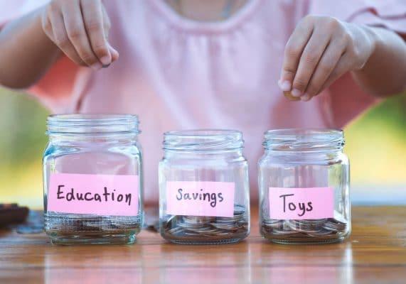 kid putting coins in jars